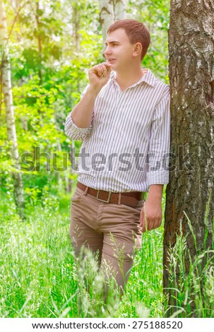 Handsome guy in spring park, standing near birch tree with straw in mouth and dreamy looking in side, spending warm sunny day outdoors - stock photo
