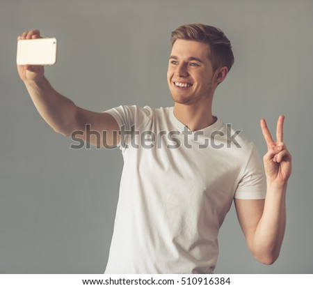 Handsome guy in white t-shirt is doing selfie using a smart phone, showing fingers and smiling, on gray background