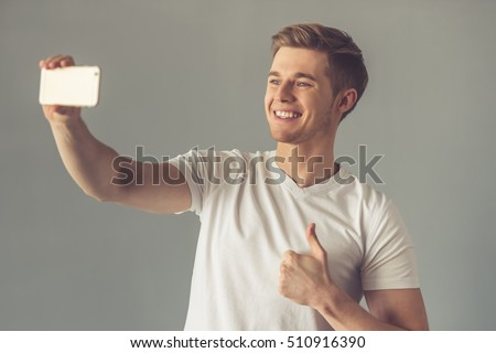 Handsome guy in white t-shirt is doing selfie using a smart phone, showing Ok sign and smiling, on gray background