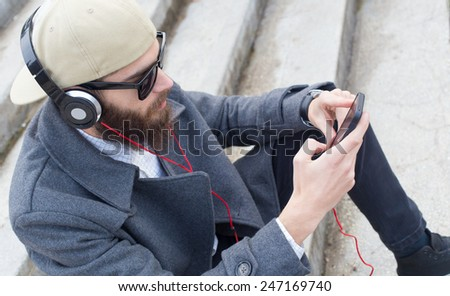 Handsome guy listening to music with heatset in his mobile. - stock photo