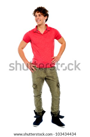 Handsome guy looking away with arms on his waist - stock photo