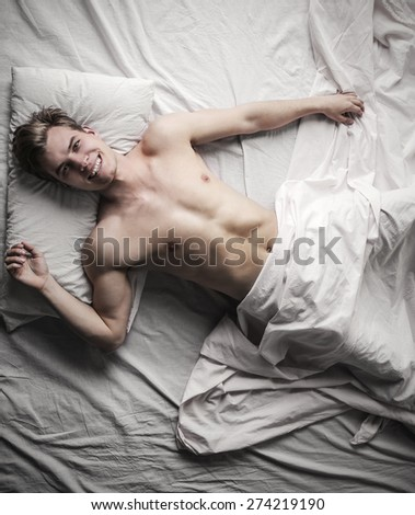 Handsome guy lying in bed - stock photo