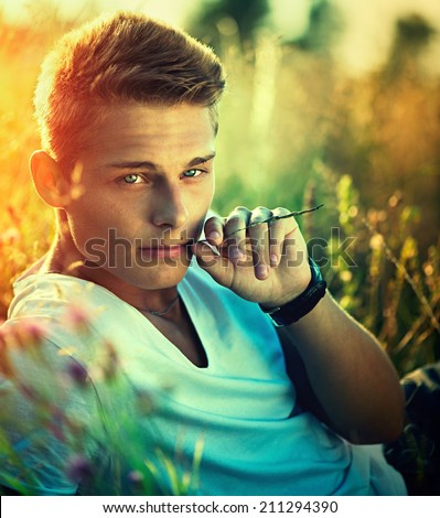 Handsome guy lying on the field. Young man enjoying nature outdoors. Looking an camera and smiling. - stock photo