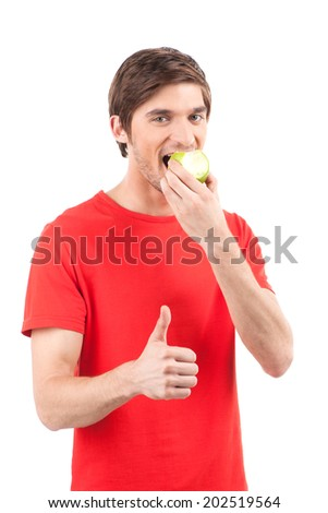 handsome guy showing thumb up on white background. portrait of man waist up eating apple
