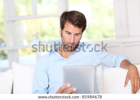 Handsome guy using electronic tablet at home