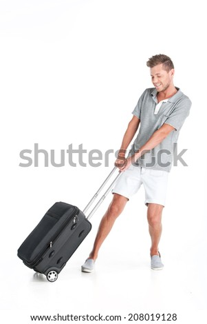 handsome guy walking with luggage and smiling. young man pulling bag on white background - stock photo