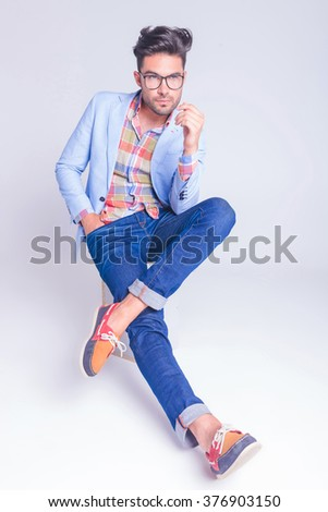 handsome guy wearing glasses and jeans posing seated with legs crossed and hand in pocket while looking away in studio background - stock photo