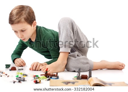 Handsome guy who is playing and building something from book - stock photo