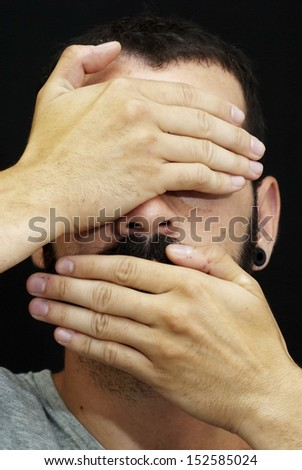 Handsome guy with beard and grey shirt, covering her face with her hand, on black background