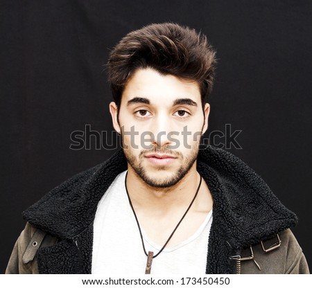 Handsome guy with beard and winter coat on black background