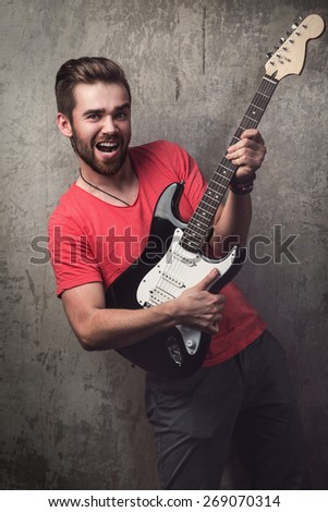 Handsome guy with electric guitar beside a dirty wall