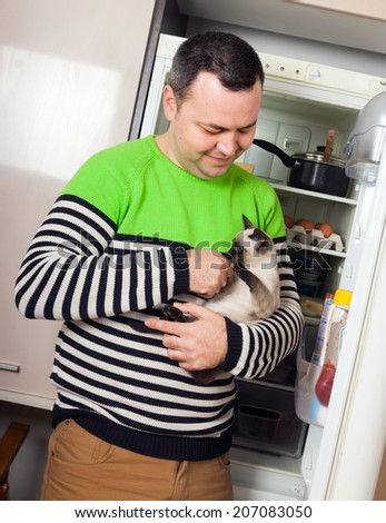 Handsome guy with kitten near opened refrigerator in kitchen at home - stock photo