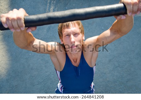 handsome guy with muscular body is trained on the bar - stock photo