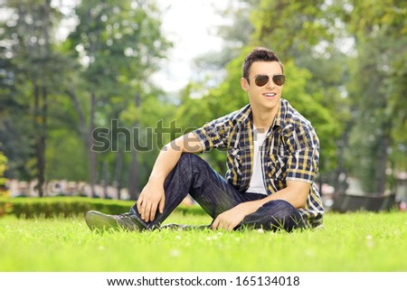 Handsome guy with sunglasses sitting on a green grass and looking at camera in a park