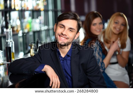 Handsome guy. Young man smiling to the camera while two girls in blurry are looking at him with interest - stock photo