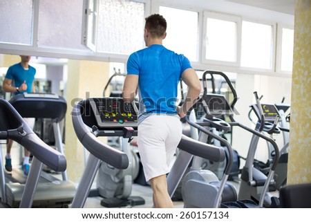Handsome gym man running on the treadmill