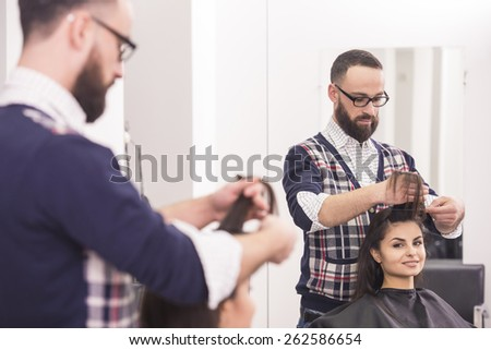 Handsome hairdresser making a haircut for a beautiful brunette girl. - stock photo