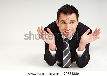 Handsome happy and thinking businessman lying, showing his hands