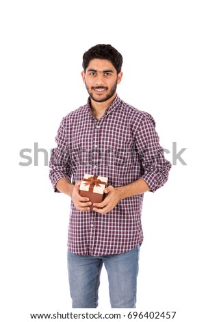 Handsome happy beard young man smiling and holding a brown gift box, guy wearing caro shirt and jeans, isolated on white background