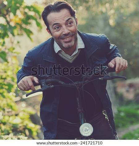 Handsome happy biker in the park, toned images