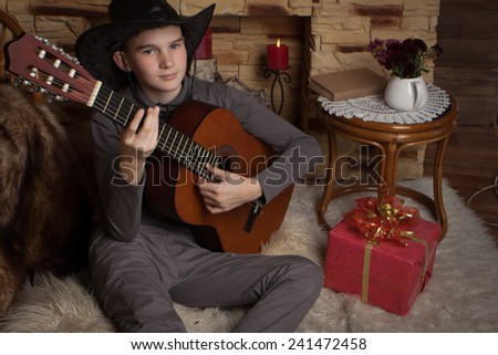 Handsome happy boy is playing on acoustic guitar  - stock photo