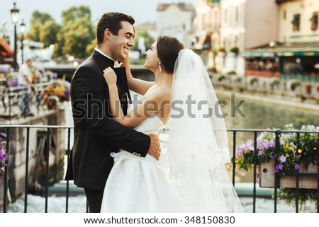 Handsome happy bride and beautiful sensual groom at romantic bridge in france closeup - stock photo