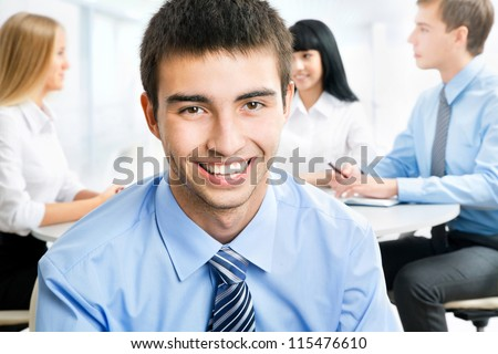 Handsome happy business man with colleagues at the back - stock photo