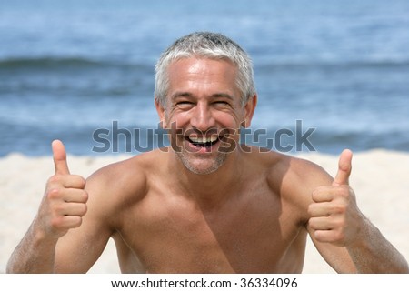 Handsome happy man giving thumbs up on the beach - stock photo