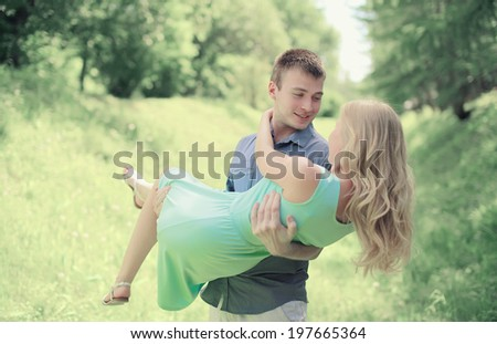 Handsome happy man holding on the hands favorite girl outdoors, warm feelings, couple, love, relationships - concept - stock photo