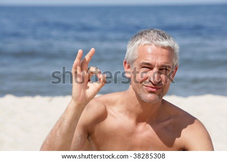 Handsome happy man indicating OK sign on the beach - stock photo
