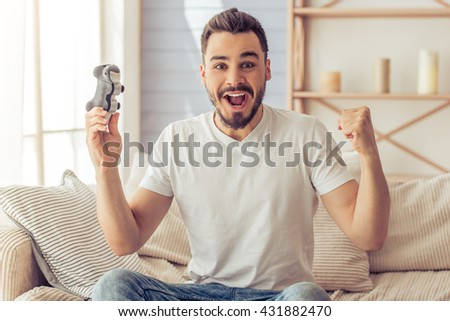 Handsome happy man is playing game console and showing success while sitting on the sofa at home - stock photo