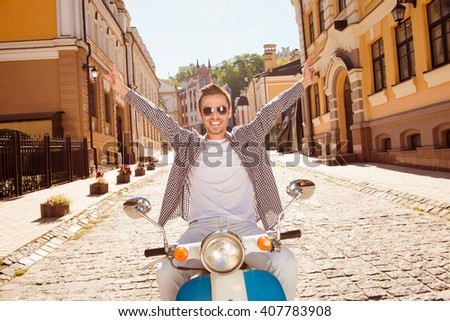 Handsome happy man riding a motorbike picking up both hands - stock photo