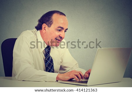 Handsome happy middle aged businessman working with laptop in office
