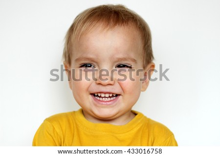 Handsome happy small toddler boy in yellow T-shirt smiling sincerely over white background, face emotions concept, indoor close-up - stock photo
