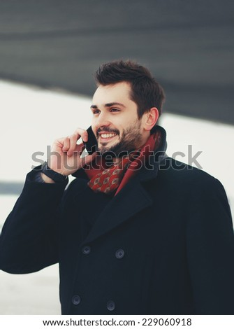 Handsome happy smiling man talking by smartphone outdoors - stock photo