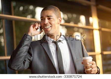 handsome happy  young businessman talking on mobile phone ,outdoors  - stock photo
