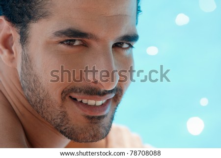 Handsome happy young hispanic man smiling and relaxing near hotel pool. Horizontal shape, headshot, copy space - stock photo