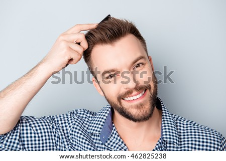 Handsome happy young man combing his hair