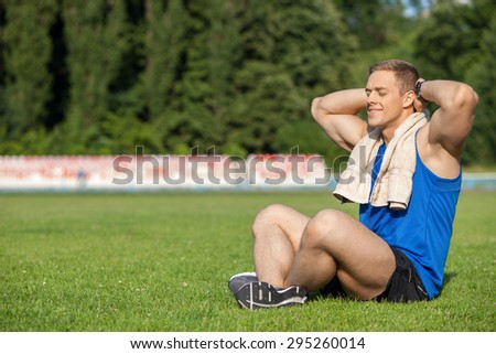 Handsome healthy athlete is sitting on green grass and resting. He has towel on his neck. The man closed his eyes with enjoyment and raised hands behind his head. Copy space in left side - stock photo
