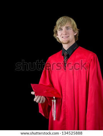 Handsome high school graduate wearing red graduation attire isolated on black - stock photo
