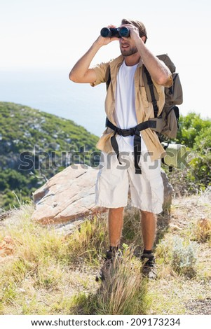 Handsome hiker looking through binoculars on a sunny day - stock photo