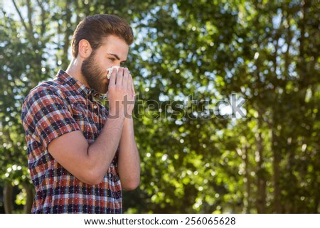 Handsome hipster blowing his nose on a summers day - stock photo