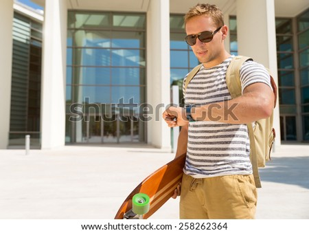Handsome hipster guy looking at his watch for the next date. Checking time for meeting with luggage and longboard on city background - stock photo