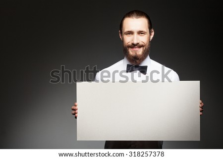 Handsome hipster guy with beard is holding a white empty placard. He is standing and smiling. Isolated on black background and copy space in left side - stock photo