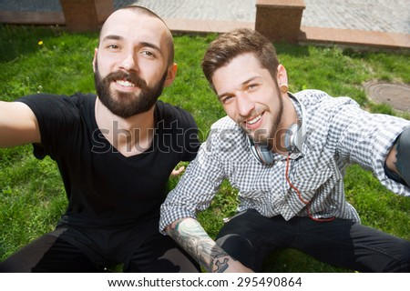 Handsome hipster guys are making selfie on grass. Their hands are stretching forward. They are laughing and looking at camera with joy - stock photo