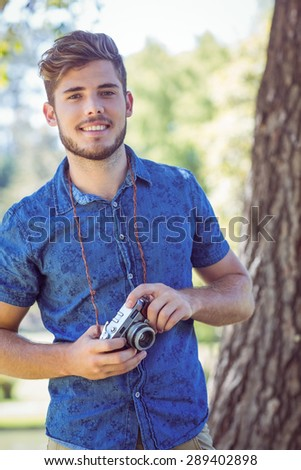 Handsome hipster holding vintage camera on a summers day