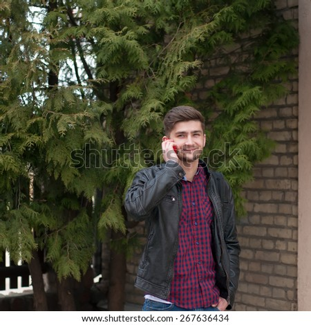 Handsome hipster in leather jacket speaking on the phone outdoor