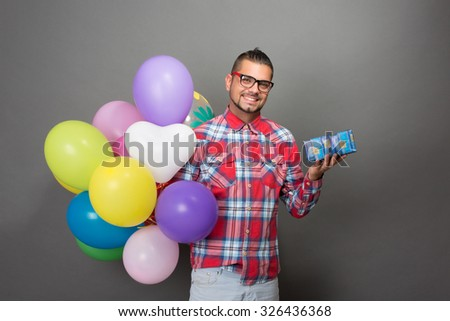 Handsome hipster man holding many multi-coloured baloons and a present in studio. Toothy smiling man in glasses going to the birthday party. - stock photo