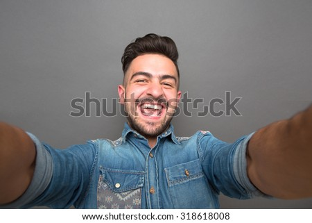 Handsome hipster man opened his mouth because of happiness. Man with fashionable haircut making selfies isolated on grey. - stock photo
