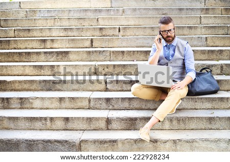 Handsome hipster modern businessman using smart phone and laptop in the city - stock photo